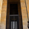 The series of doors to the mausoleum have security grilles.